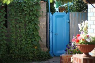 Вход в часть двора с летними душами и туалетами